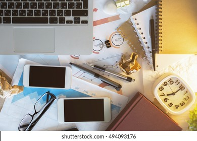 Top view of messy office workplace with two blank cellular phones, financial reports, supplies, laptop keyboard, clock and other items. Mock up