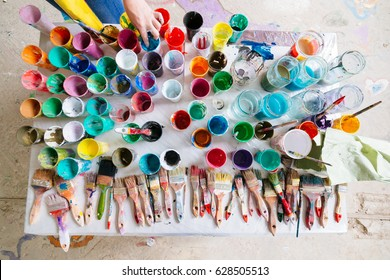Top view of a messy table full of dirty paintbrushes, jars and glasses filled with different mixed paints. A hand taking a jar can be seen above