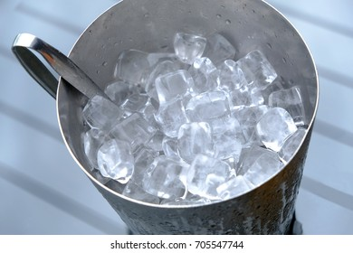 Top view of metal ice bucket on table with tong preparing for serving with drink or beverage menu