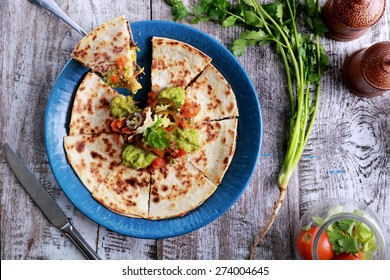 top view mexican cuisine quesadilla served at blue plate with guacamole, salsa and jalapenos