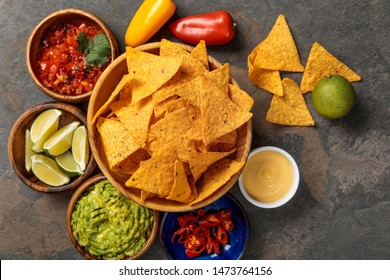 top view of Mexican nachos served with guacamole, limes, cheese sauce and salsa on stone table
