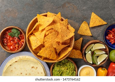 top view of Mexican nachos served with tortilla, guacamole, cheese sauce and salsa on stone table