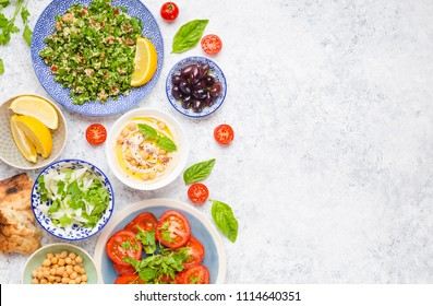 Top view of Middle eastern or arab dishes and assorted snacks on concrete white rustic background with copy space: hummus, pita, tabbouleh vegetable salad, olives, chickpeas, tomatoes, pomegranate