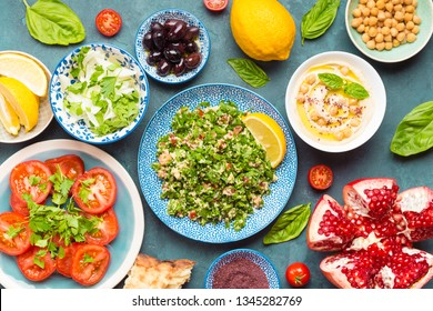 Top view of Middle eastern or arab dishes and assorted meze and snacks on concrete blue rustic background: hummus, pita, tabbouleh vegetable salad, olives, chickpeas, tomatoes, pomegranate, herbs