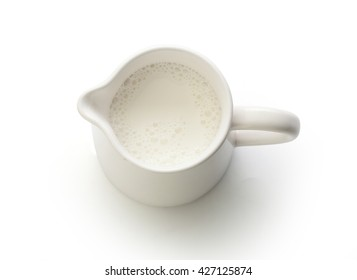 Top view of milk jug with milk on the white