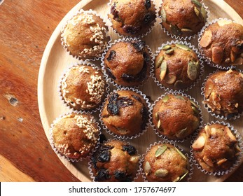 Top view mini muffin with sesame, raisin, cranberry, pumpkin seed and macadamia nut topping on wooden table