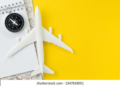 top view of miniature airplane, compass, notepad and map on vivid yellow background table with blank copy space.
