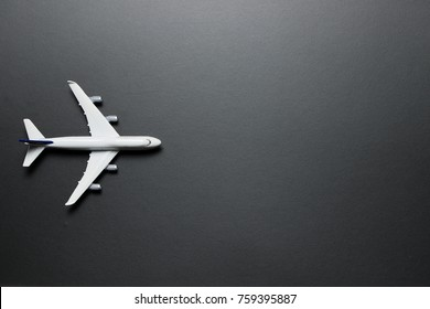 Top view of miniature airplane on black background, with copy space