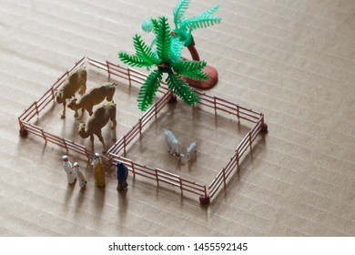 Top view of miniature toy Arab man and wife in abaya buys camel and sheep from a kid on a farm concept.