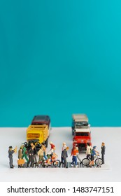 Top view of miniature toys of crowd walking on zebra crossing with vehicles stopped concept.