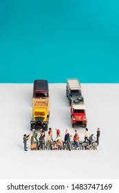 Top view of miniature toys of crowd walking on zebra crossing with vehicles stopped concept - illustrative editorial
