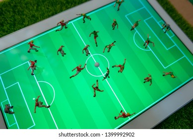 Top view of miniature toys figurines football (soccer) players on a computer pad.