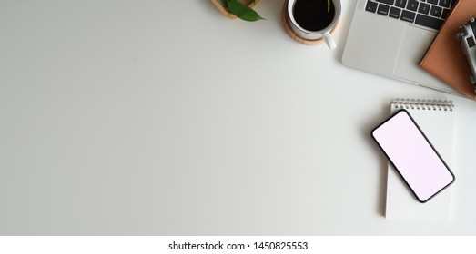 Top view of minimal workspace with blank screen smartphone, laptop on white color desk