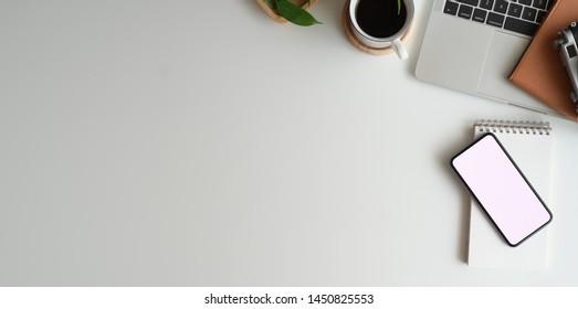 Draufsicht auf minimalen Arbeitsplatz mit kleinem Bildschirm-Smartphone, Notebook auf weißem Schreibtisch