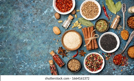 Top view of mix bright spices and herbs in small bowls and bottles as ingredient for healthy food on blue concrete background with copy space