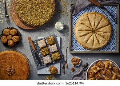 Top view Mixed Oriental sweet desserts, Kunafa, Basbousa, Nuts, Goulash on a grey textured wooden background