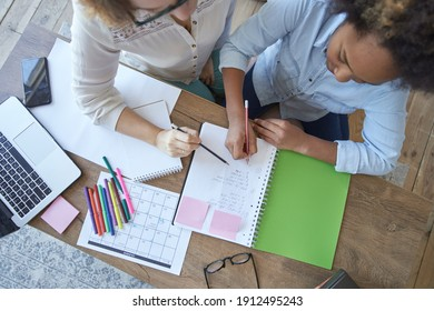 Top view of mixed race teen girl doing math task, school homework together with female teacher in the living room at home