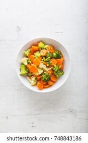 Top of view mixed vegetable carrot broccoli and cauliflower in bowl on white concrete background.