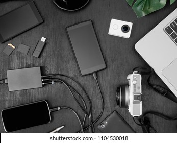 top view Mobile phone charging on USB Wall Charger on black table background.