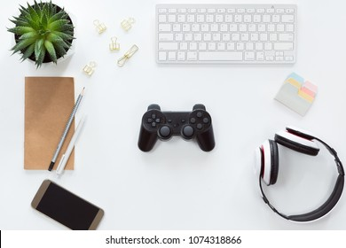 Top view of mobile phone, computer keyboard, notebook on white background, flat lay with joystick and gamepad, game console, headphones