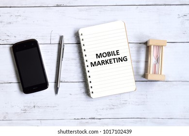 Top view of mobile phone,pen,hourglass and notebook written with 'MOBILE MARKETING' on white wooden background.
