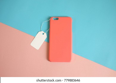 Top view of mock up clear phone case salmon or orange color with price tag on colorful background, copy space, sale space, branding design, corporate identity