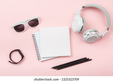 Top view mock up notebook with Fitness tracker, headphones, glasses on pink background. Copy space. 'To do' list. Planning, results of walk route, to-do list or shopping. Smart Band Sport bracelet app