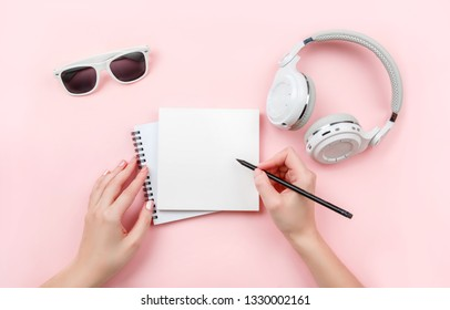 Top view mock up woman's hands with notebook, headphones, glasses on pink background. Copy space. 'To do' list. Planning, results of walk route, to-do list or shopping. Relax, wish list, play list