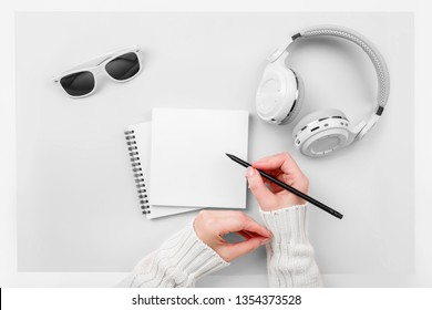 Top view mock up woman's hands with notebook, headphones, glasses on pink background. Copy space. 'To do' list. Planning of winter walk route, to-do list or shopping. Relax, wish list, play list