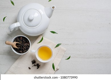Top view mockup a cup of tea and tea leaf on the white desk. Free space for your text.