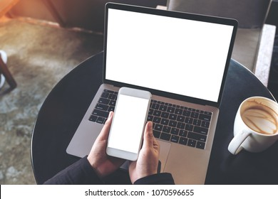 Top view mockup image of hands holding blank mobile phone while using laptop with blank white desktop screen on table