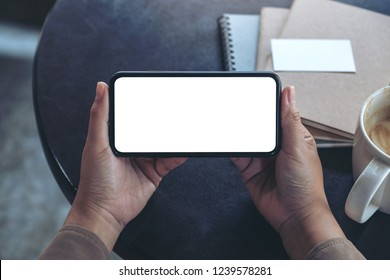 Top view mockup image of hands holding and using a black mobile phone with blank screen horizontally for watching with coffee cup and notebooks on table - Shutterstock ID 1239578281