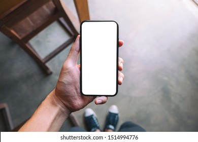 Top view mockup image of a man standing and holding black mobile phone with blank white screen