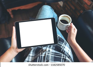 Top view mockup image of a woman sitting cross legged and holding black tablet pc with blank white desktop screen while drinking coffee in cafe