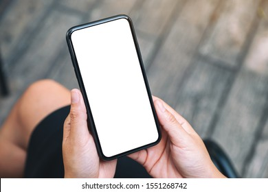 Top view mockup image of a woman holding a black mobile phone with blank white desktop screen