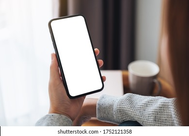 Top view mockup image of a woman holding mobile phone with blank desktop screen while sitting in bed room at home