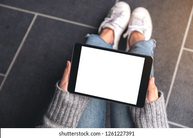Top view mockup image of woman's hands holding and using black tablet pc with blank white desktop screen while sitting on the floor