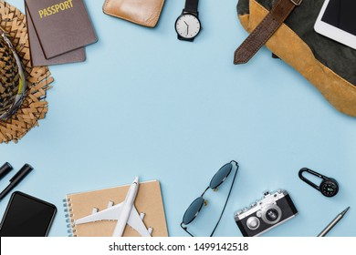 Top view mockup of Traveler's accessories with passport, books of travel plan, wallet, camera, hat, backpack and airplane toy isolated colorful blue background with empty space,Tropical travel concept
