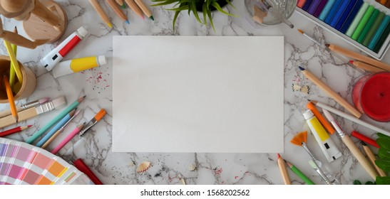 Top view of modern artist workspace with sketch paper and painting tools on marble desk background