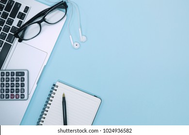 Top view of Modern blue office desk table with laptop and blank notebook page , calculator, glasses, earphone, pen for input the text on pastel blue background.Copy space for word.empty page.