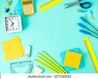 Top view of modern bright blue office desktop with school supplies on table around empty space for text. Back to school concept.