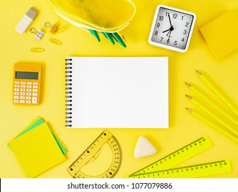 Top view of modern bright yellow office desktop with blank notepad, school supplies on table, empty space for text. Back to school concept.