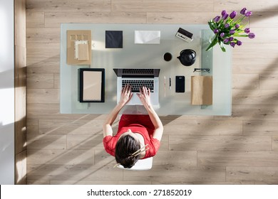 top view, Modern businesswoman sitting at glass desk and working on her laptop, her table is perfectly tidy, the sun casts graphics shadows on the wood floor