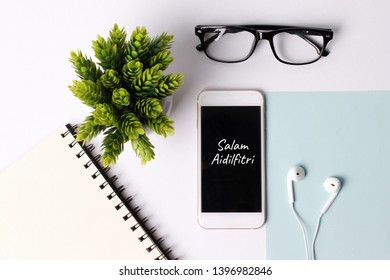"Top view modern concept for eid mubarak celebcration, smartphone, glasses and earphone writing ""Salam Aidilfitri"""