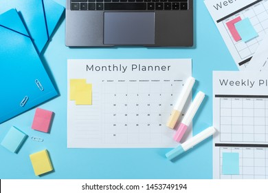 Top view of modern laptop, colorful stationery and monthly planner with copy space on pastel blue background