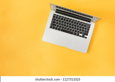 Top view of modern laptop isolated on yellow background.