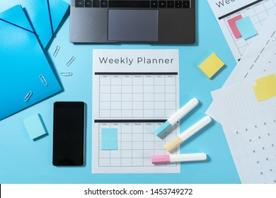Top view of modern laptop, smartphone, colorful stationery and weekly planner with copy space on pastel blue background