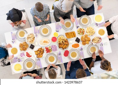 top view of modern multiethnic muslim family praying before having iftar dinner together during a ramadan feast at home