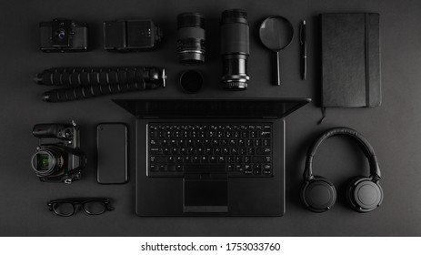 Top view of modern photographer desk with camera gear, laptop and headphones. Black technology dark flat lay. Equipment arranged on the table.