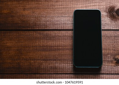 Top view of a modern smartphone with large screen on vintage wooden table. Blank empty display. Mock up